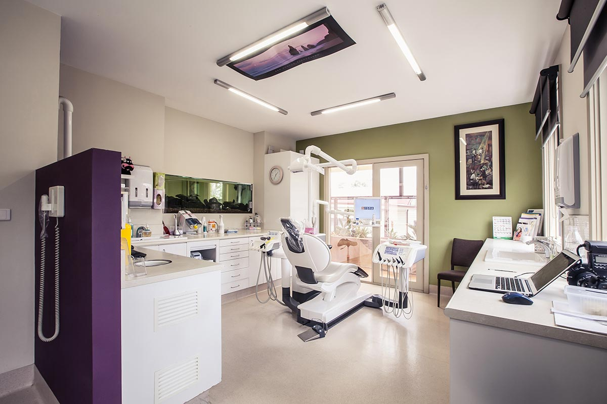 A photo of a high tech dental office with a TV on the ceiling.